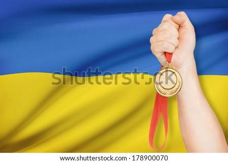 Sportsman holding gold medal with flag on background - Ukraine - stock photo