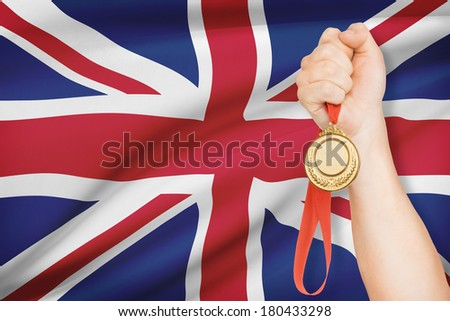 Sportsman holding gold medal with flag on background - United Kingdom of Great Britain and Northern Ireland - stock photo