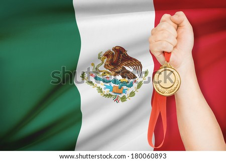Sportsman holding gold medal with flag on background - United Mexican States