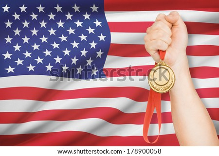 Sportsman holding gold medal with flag on background - United States of America - stock photo