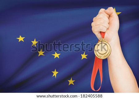 Sportsman holding gold medal with State of Alaska flag on background. Part of a series. - stock photo