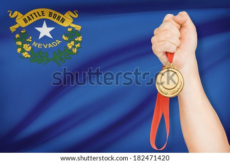 Sportsman holding gold medal with State of Nevada flag on background. Part of a series. - stock photo