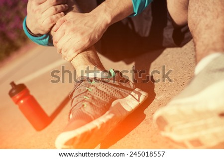 sportsman holding his leg in the park and bottle of water near