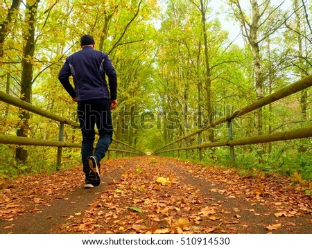 Sportsman in  black sportswear run on road. The man is slowly running on asphalt way covered by autumn leaves. Pathway in park, beeches and maples leaves.