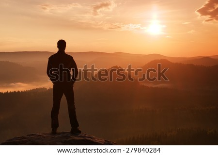 Sportsman in black with hands in pockets stand on the peak in rock empires park and watching over the misty and foggy morning valley to Sun.  - stock photo