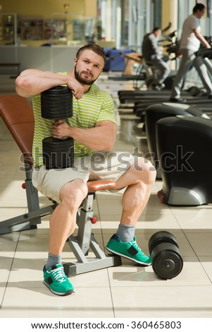 Sportsman in gym. Bodybuilder sitting in gym. Man keeps dumbbell in hand. Dumbbells on the floor near man's feet.