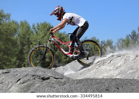 Sportsman in sportswear on a mountain bike rides on the stones trail in the extreme style of downhill