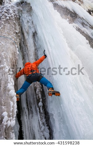 Sportsman is climbing on the frozen waterfall with crampons and ice tools - stock photo
