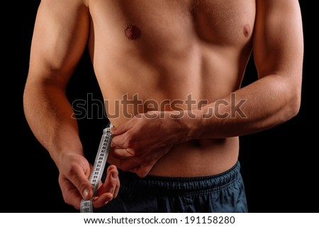 Sportsman is measuring waist with tape on a black background - stock photo