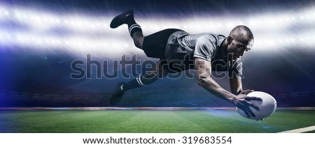 Sportsman jumping for catching rugby ball against rugby stadium - stock photo
