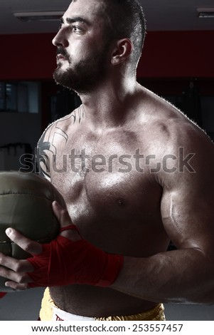 Sportsman kick boxer intense portrait against grey background. Young Boxer fighter .