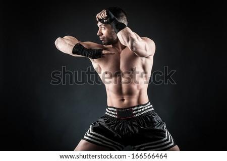 Sportsman kick boxer portrait against black background.  - stock photo