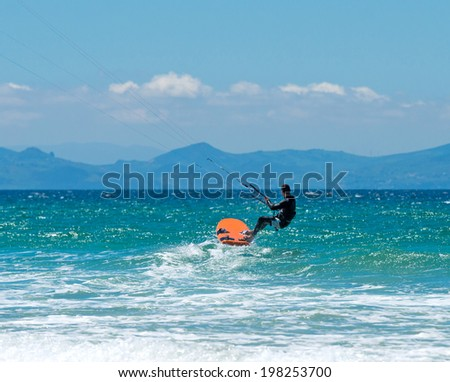 sportsman kite sergfer on clean beach on a background of mountains  in summer day