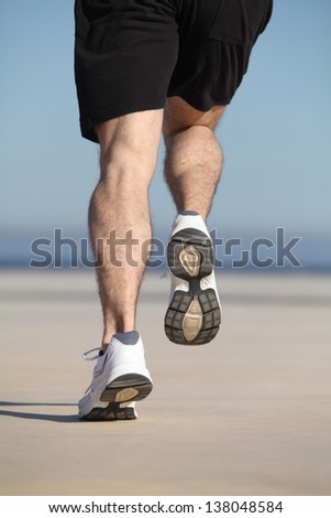 Sportsman legs running on the concrete of a seafront on the concrete of a seafront with the sky in the background - stock photo