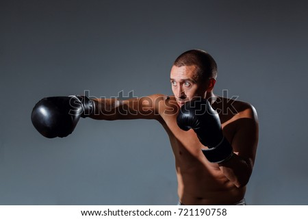 Sportsman muay thai boxer fighting in boxing cage. Sport concept.