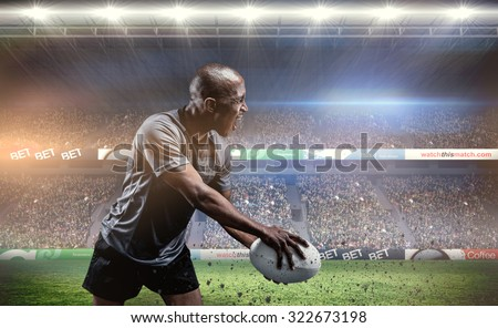 Sportsman playing rugby against rugby stadium - stock photo