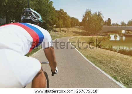 Sportsman riding a bike into the park with lake - Outdoor activity with bicycle and green nature - stock photo