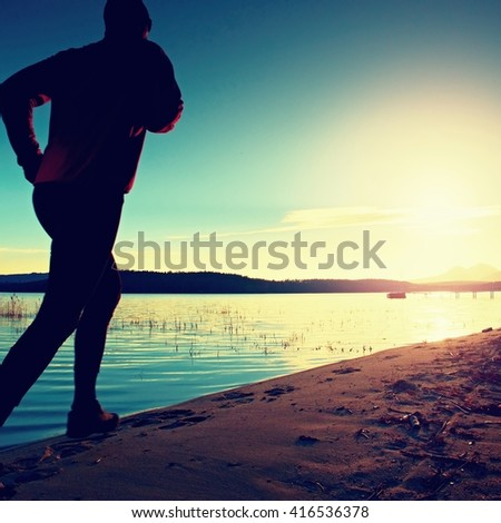 Sportsman running at amazing summer sunset along coastline in sport and healthy positive lifestyle concept