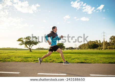 sportsman running in the park in sunset