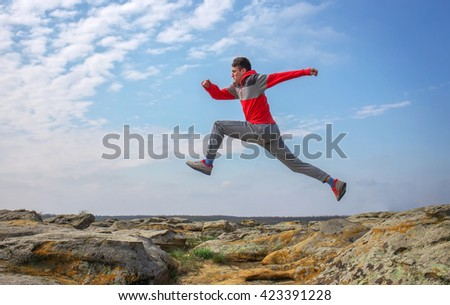 Sportsman running, jumping over rocks in mountain area.    - stock photo