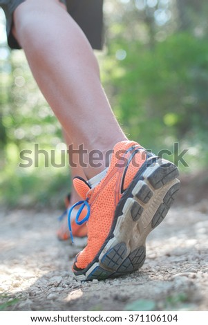 sportsman's legs standing on the grass in running shoes close up