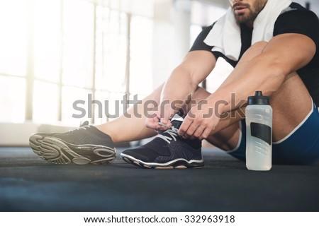 Sportsman ties his black sneakers - stock photo