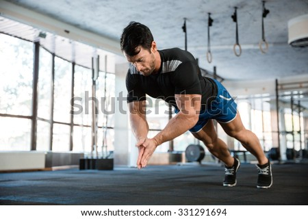 Sportsman wearing blue shorts and black t-shirt doing push-up with claping - stock photo