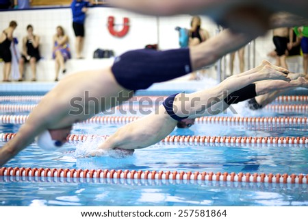 Sportsmen diving into a swimming pool - stock photo