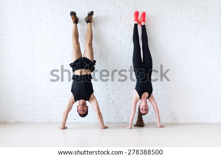 sportsmen woman and man doing a handstand against wall concept balance sport fitness lifestyle and people. - stock photo