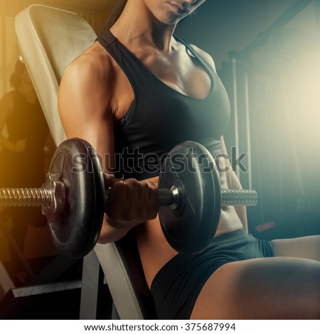 sportswoman do exercises with dumbbells - stock photo