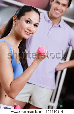 Sportswoman exercises in fitness gym with couch - stock photo