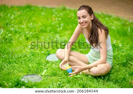 Sportswoman have a rest sitting on the grass with badminton - stock photo