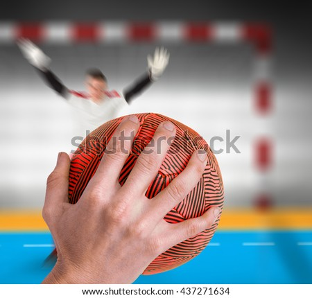Sportswoman holding a ball against handball field indoor - stock photo