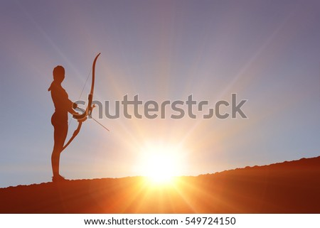 Sportswoman practicing archery against clouds