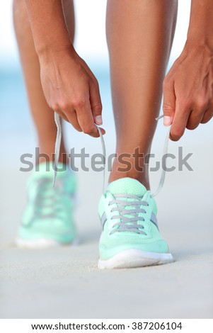 Sportswoman runner getting ready tying running shoes on beach. Fitness woman living a healthy and active life preparing for cardio training. Wellness and health concept. - stock photo