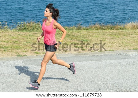 Sportswoman running fast on blue sea background. Caucasian brunette young model exercising on summer day. - stock photo