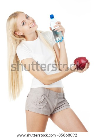 Sportswoman with a bottle of mineral water and red apple, isolated on white background