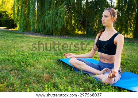 Sportswoman with long hair meditating on a yoga mat outdoor in summer afternoon