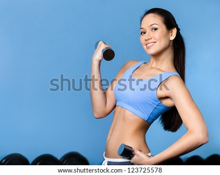 Sportswoman works out with dumbbells in gym - stock photo