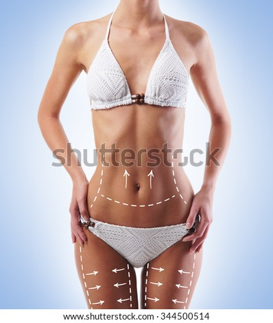 Sporty and fit girls body with arrows. Fat lose, liposuction and cellulite removal concept. - stock photo