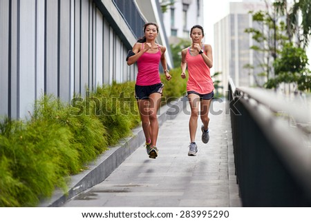 sporty asian chinese woman running downhill outdoors for morning workout - stock photo