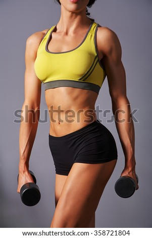 sporty attractive fitness woman with dumbbells in gym. trained female body
