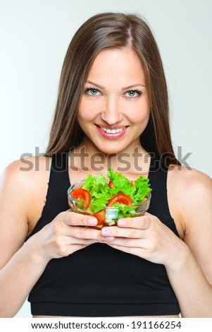 sporty attractive woman eating vegetables salad. healthy food. slim girl. - stock photo