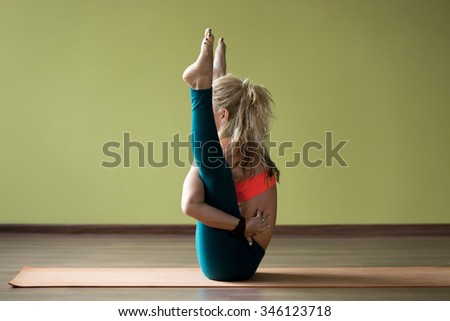 Sporty beautiful blond young woman in sportswear working out indoors, doing hip-opening yoga training, exercises for groins, hips, thighs and calf muscles flexibility on orange mat, full length - stock photo