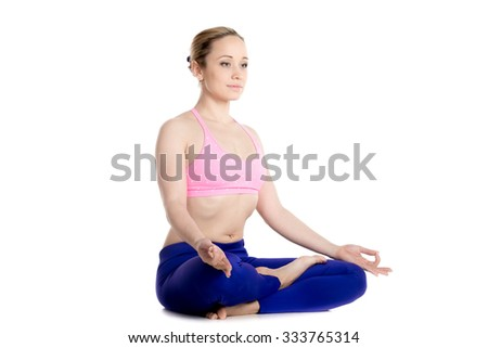 Sporty beautiful blond young woman sitting cross-legged in Ardha Padmasana, half lotus posture, meditating, breathing, studio full length on white background, isolated shot, three-quarters view - stock photo