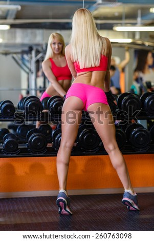 Sporty beautiful woman stands in the gym. Fitness. - stock photo