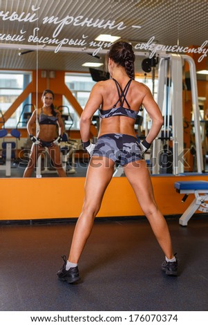 Sporty beautiful woman stands in the gym. Posing and showing muscle.  Fitness girl.