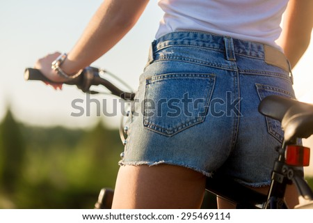 Sporty beautiful young woman butt on bike on summer day, close up, back view - stock photo
