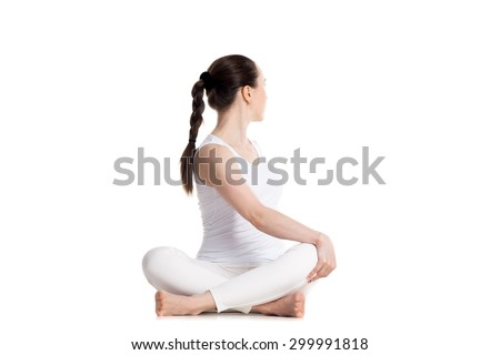Sporty beautiful young woman in white sportswear practicing yoga, sitting cross legged in Revolved easy pose, spinal twist, parivrtta sukhasana, studio full length isolated shot, front view - stock photo