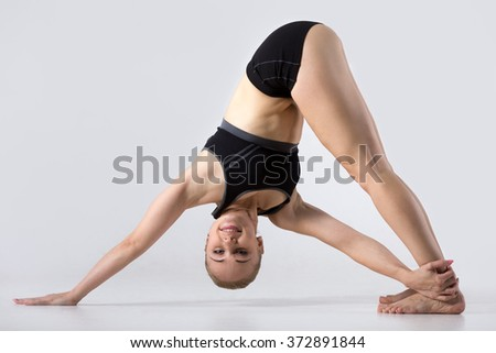 Sporty beautiful young woman practicing yoga, doing Revolved Downward-Facing Dog Pose, Parivrtta Adho Mukha Svanasana, working out wearing black sportswear, studio, full length, side view